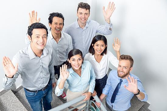 joyful-business-team-waving-office-stairway_1262-5220